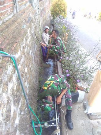 Anggota TNI  Bersama Masyarakat Desa Telaga Kerja Bakti Bersih Lingkungan